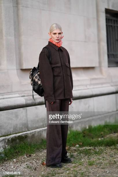 Model wears a red scarf, a brown oversized wool jacket, pants, black leather shoes, a black and white houndstooth pattern printed backpack bag,...