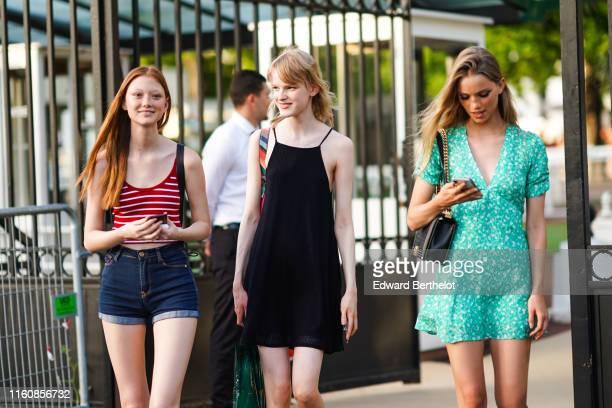 Model wears a red tank crop top with white thin stripes, navy blue denim cuffed shorts ; A model wears a black strappy mini dress, outside Miu Miu...
