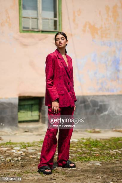 Model wears a red with black print pattern blacker jacket, matching red with black print pattern suit pants, black shiny leather puffy strappy...