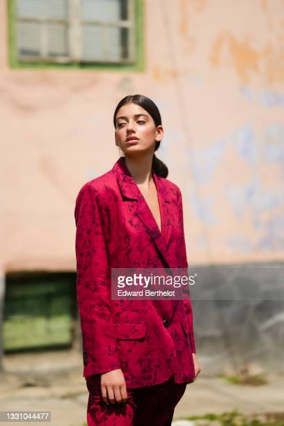 Model wears a red with black print pattern blacker jacket, matching red with black print pattern suit pants, on July 22, 2021 in Sibiu, Romania.
