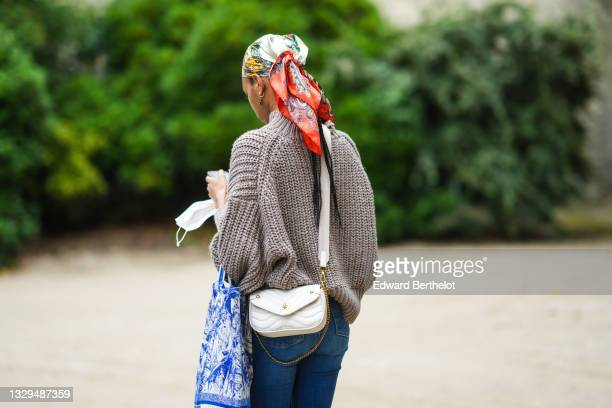 Model wears a red / yellow / gold / black print pattern silk scarf, a brown turtleneck ribbed wool pullover, blue denim flared jeans pants, a blue...