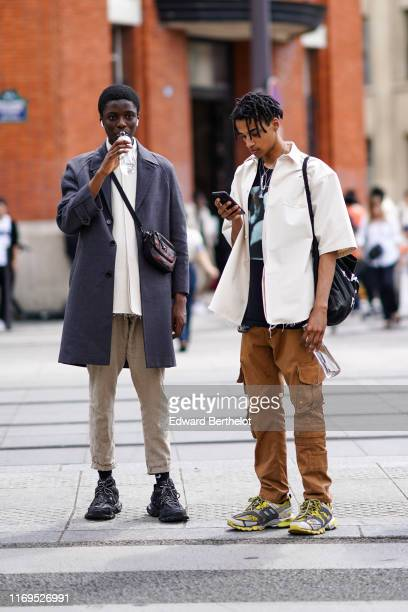 A model wears a rippedhem white shirt a grey coat a beltbag beige cuffed pants black Balenciaga sneakers A model wears a black tshirt with a blue...