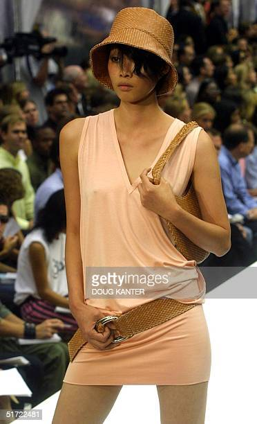 A model wears a salmon jersey vneck tshirt dress with dring hip belt diamond patterned leather bucket hat and diamond patterned circular bag at the...