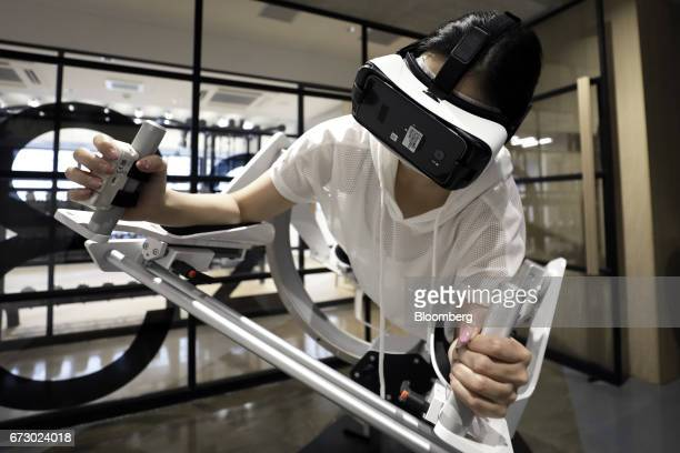 A model wears a Samsung Electronics Co Gear virtual reality headset as she demonstrates using the Icaros VR fitness machine manufactured by Icaros...
