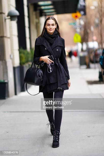 Model wears a scarf, a dark double breasted jacket a black leather bag, black leggings, black shoes, during New York Fashion Week Fall Winter 2020,...