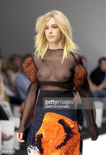 A model wears a seethrough blouse and patterned denim skirt from the collection of Julian And Sophie 12 September 2002 during the London Fashion Week