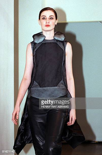 A model wears a silk organza body vest with black silk organza neck rest black leather pants and a black leather coat during the Helmut Lang fashion...