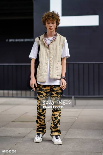 A model wears a sleeveless jacket a white tshirt military camo print pants white sneakers shoes during London Fashion Week Men's June 2018 on June 10...