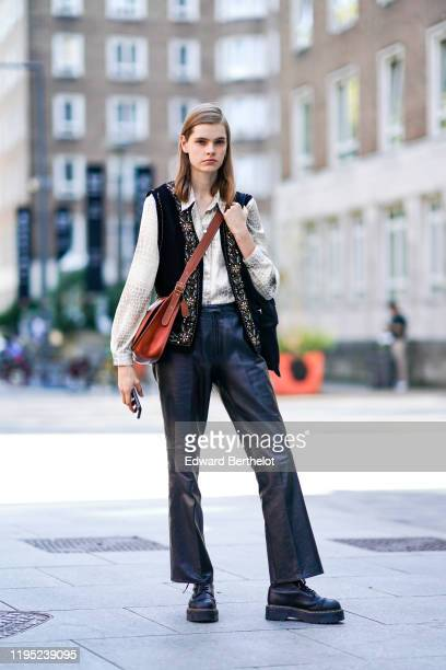 Model wears a sleeveless jacket with embroidery, a crocodile pattern print shirt, black leather flare pants, black leather shoes, a brown shoulder...