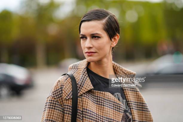 Model wears a t-shirt, a brown checked trench coat, outside Chanel, during Paris Fashion Week - Womenswear Spring Summer 2021, on October 06, 2020 in...
