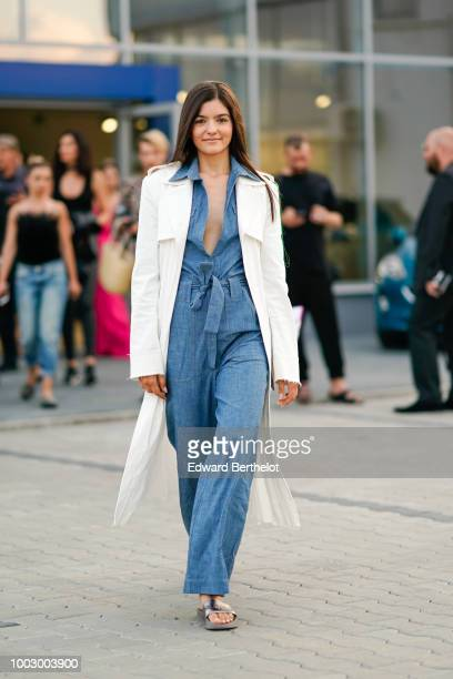 A model wears a white coat a blue denim jumpsuit with flared pants during Feeric Fashion Week 2018 on July 20 2018 in Sibiu Romania