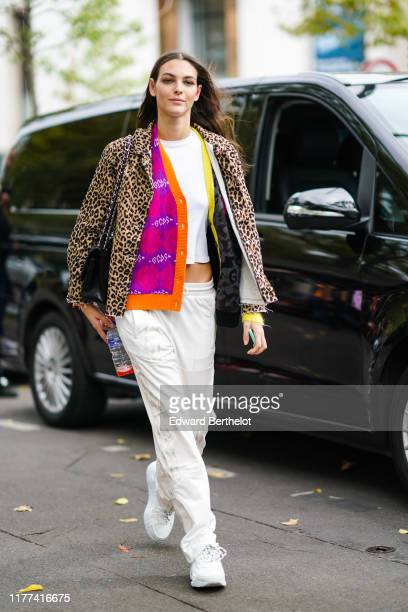 Model wears a white crop top, a purple/ orange and yellow/grey jacket, a leopard print ripped hem jacket, Adidas cream-color sport pants, white...