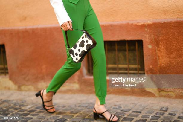 Model wears a white cropped blazer jacket, green laces high waist pants, a black and white cow print pattern handbag, black leather strappy block...