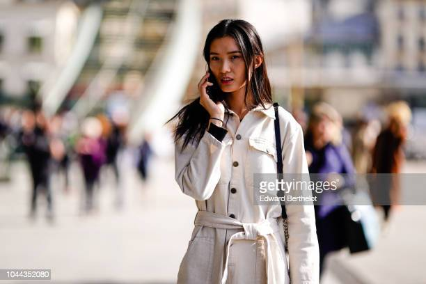 A model wears a white jumpsuit outside Giambattista Valli during Paris Fashion Week Womenswear Spring/Summer 2019 on October 1 2018 in Paris France