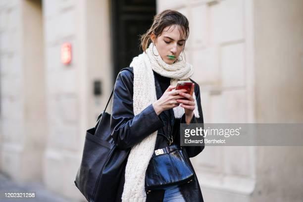 Model wears a white long scarf, a black long coat, a black leather bag, blue denim jeans pants, a tote bag, outside Maison Margiela, during Paris...