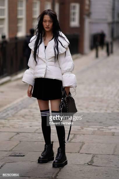 A model wears a white puffer coat a black skirt thigh high black socks black shoes a black bag during London Fashion Week September 2017 on September...