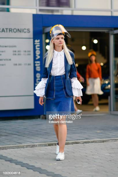 A model wears a white shirt a blue denim jacket a blue denim skirt white sneakers white flared sleeves during Feeric Fashion Week 2018 on July 20...