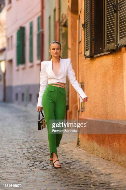 Model wears a white shoulder pads / V-neck / cropped blazer jacket, green laces high waist ribbed pants, a black and white cow print pattern handbag,...