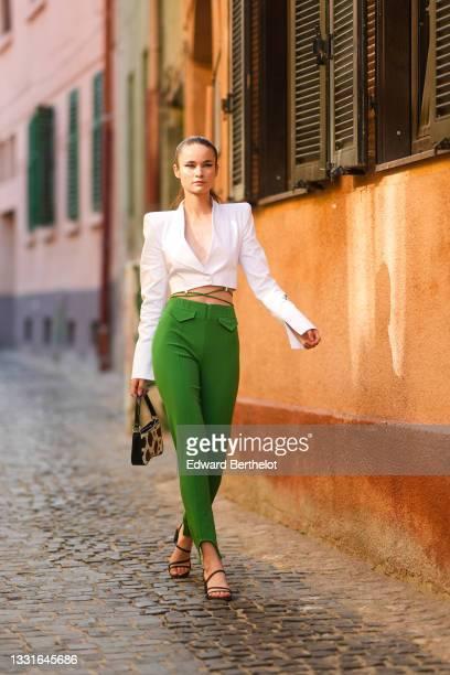 Model wears a white shoulder pads / V-neck / cropped blazer jacket, green laces high waist pants, a black and white cow print pattern handbag, black...