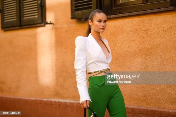 Model wears a white shoulder pads / V-neck / cropped blazer jacket, green laces high waist pants, a black handbag, after the Ramelle show, during...