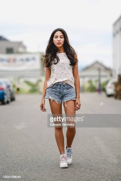 A model wears a white sleeveless top blue denim shorts during Feeric Fashion Week 2018 on July 22 2018 in Sibiu Romania