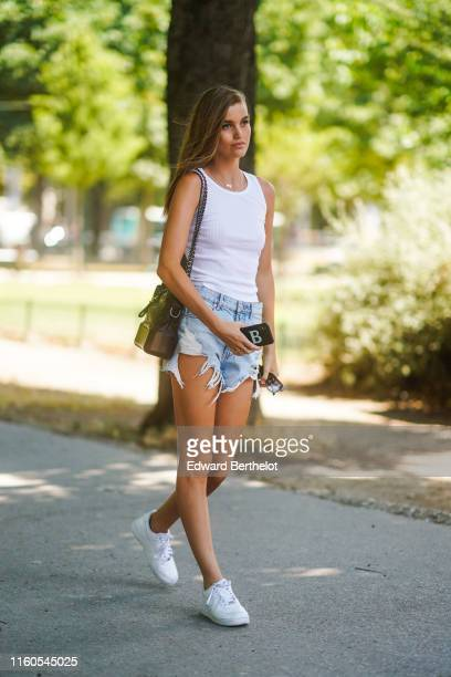 A model wears a white tank top blue ripped shorts white sneakers a bag outside Chanel during Paris Fashion Week Haute Couture Fall/Winter 2019/2020...