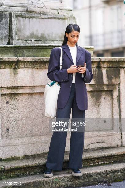 Model wears a white t-shirt, a gray oversized blazer jacket, a tote bag, suit flare pants, shoes, outside Koche x Pucci, during Milan Fashion Week...