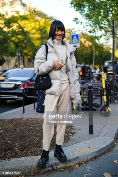 Model wears a white turtleneck, a white puffer jacket, a black Prada bag, white pants, black leather shoes outside Shiatzy Chen, during Paris Fashion...