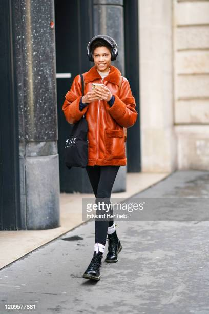 Model wears a white turtleneck, an orange shearling jacket, a black tote bag, black leggings, white socks, black army-style ankle-boots, during Paris...