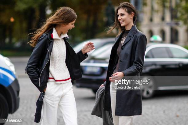 Model wears a white wool knitted pullover, a black leather jacket, white pants ; a model wears, a black leather jacket, a brown pullover with a...