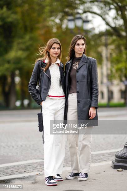Model wears a white wool knitted pullover, a black leather jacket, white pants, sneakers ; a model wears, a black leather jacket, a brown pullover...