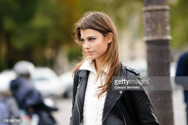 Model wears a white wool knitted pullover, a black leather jacket, outside Chanel , during Paris Fashion Week - Womenswear Spring Summer 2021, on...
