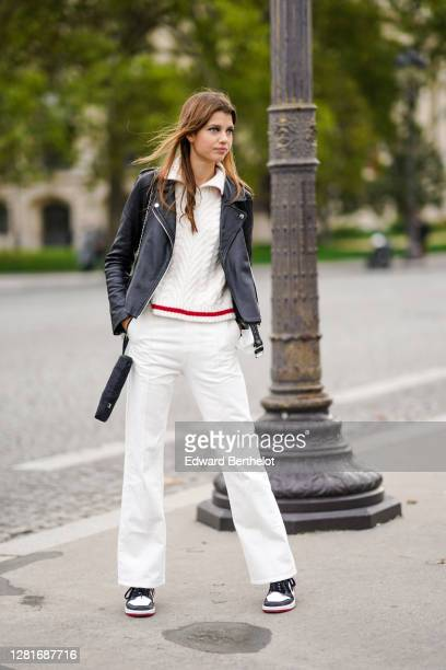 Model wears a white wool knitted pullover, a black leather jacket, white pants, sneakers, outside Chanel , during Paris Fashion Week - Womenswear...