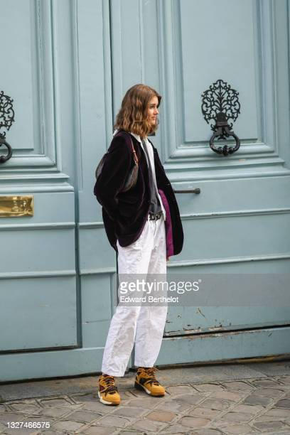 Model wears a white zipper sweater, a black t-shirt, a black long blazer jacket, a brown CC monogram in coated canvas shoulder bag from Celine, white...