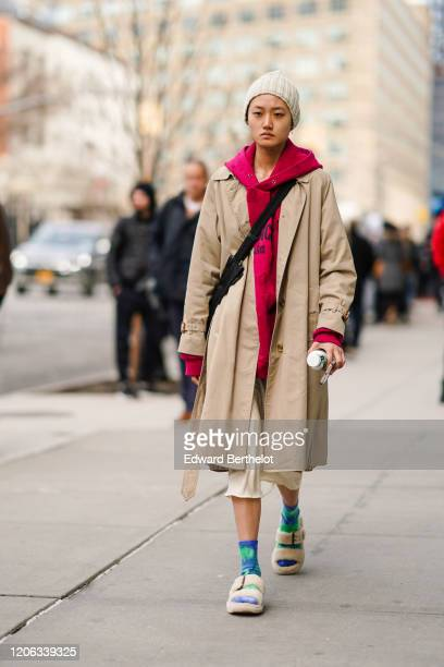 A model wears a wool beanie hat a pink hoodie sweater a beige coat blue and green socks fluffy sandals during New York Fashion Week Fall Winter 2020...