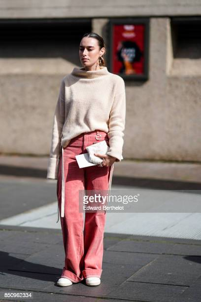 A model wears a wool turtleneck top pink flared pants white sneakers outside Roland Mouret during London Fashion Week September 2017 on September 17...