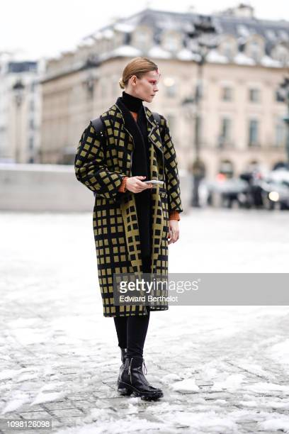 A model wears a yellow and black checked coat outside Alexis Mabille during Paris Fashion Week Haute Couture Spring Summer 2020 on January 22 2019 in...