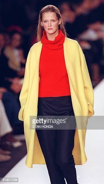 A model wears a yellow double face cashmere coat over a red cashmere funnel neck shell and black felt pants during the Ralph Lauren fashion show 17...