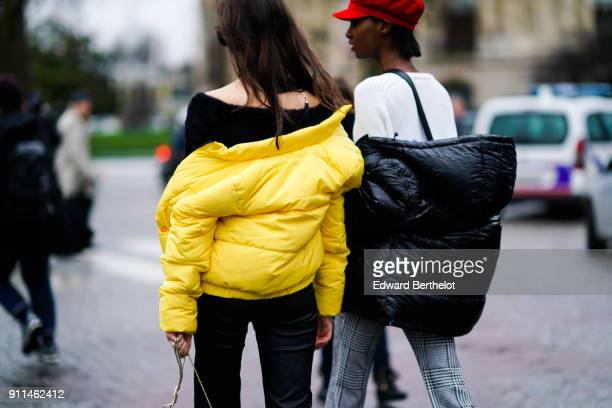 A model wears a yellow puffer coat and a black tshirt a model wears a black puffer coat and a white top outside Chanel during Paris Fashion Week...