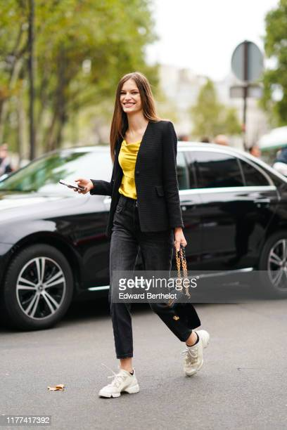 Model wears a yellow top, a black jacket, a black suede bag, black denim pants, cream-color Dior sneakers, outside Redemption, during Paris Fashion...