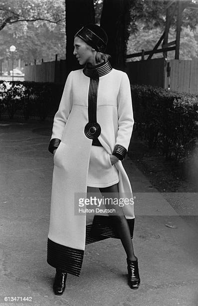 A model wears an anklelength coat over a miniskirt of matching fabric from a collection by French designer Pierre Cardin August 1969