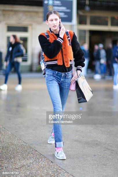 A model wears an orange faux fur coat a black top blue denim jeans pants pink socks and shoes outside the Olivier Theyskens show during Paris Fashion...