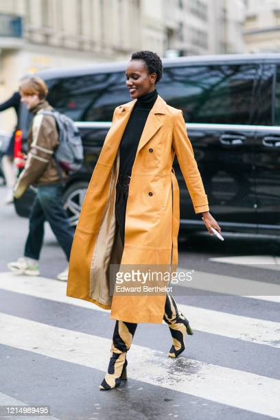 Model wears an orange long trench coat, a black turtleneck pullover, beige and black zebra print pattern pointy boots, outside Ralph & Russo, during...
