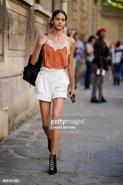A model wears an orange top white shorts balck shoes outside the Valentino show during Paris Fashion Week Haute Couture Fall/Winter 20172018 on July...