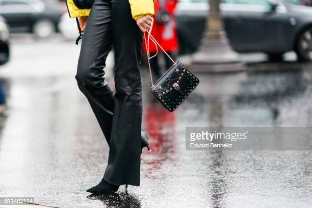 A model wears black flare pants a black leather bag outside Chanel during Paris Fashion Week Haute Couture Spring/Summer 2018 on January 23 2018 in...