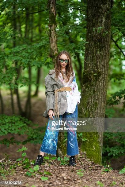 Model wears black sunglasses, a gold metal large pendant necklace, a white with multicolored paint pattern oversized shirt, a brown leather belt, a...