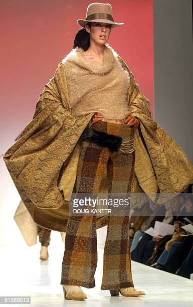 A model wears checkered flared pants with long sleeved beige angora wool sweater with poncho at the Manuel Fernandez show during Fall 2001 Fashion...