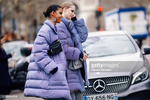 Model wears earrings, a black bag, a purple striped puffer coat ; a model wears a grey bag, a blue striped puffer coat, outside Altuzarra, during...
