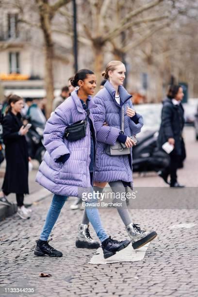 Model wears earrings, a black bag, a purple striped puffer coat, jeans, black lace up sneakers ; a model wears a grey bag, a blue striped puffer...