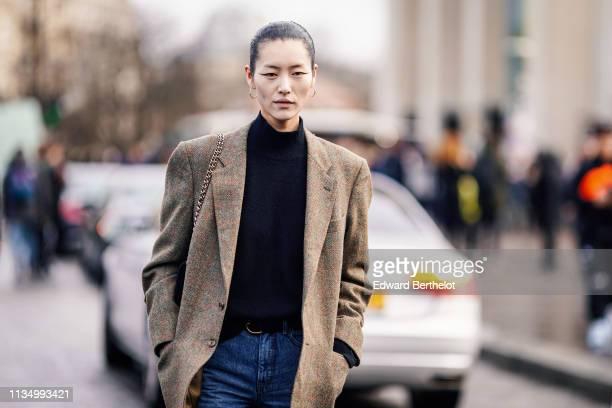 A model wears earrings a hineck black sweater a light brown tweed jacket jeans outside Haider Ackermann during Paris Fashion Week Womenswear...